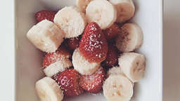 Banana and strawberry bowl with coconut and dark chocolate (85%)